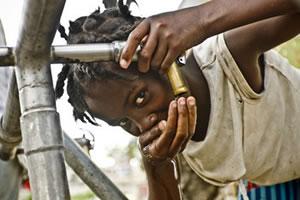 Una niña bebe agua en un punto de distribución del campo de desplazados de la Universite de Quisqueya en Puerto Príncipe. (c) Pablo Tosco / Intermón Oxfam