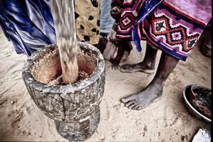 Un grupo de mujeres moliendo cereales en un mortero en el campo de refugiados sudaneses de Djabal. (c) Pablo Tosco / Intermón Oxfam